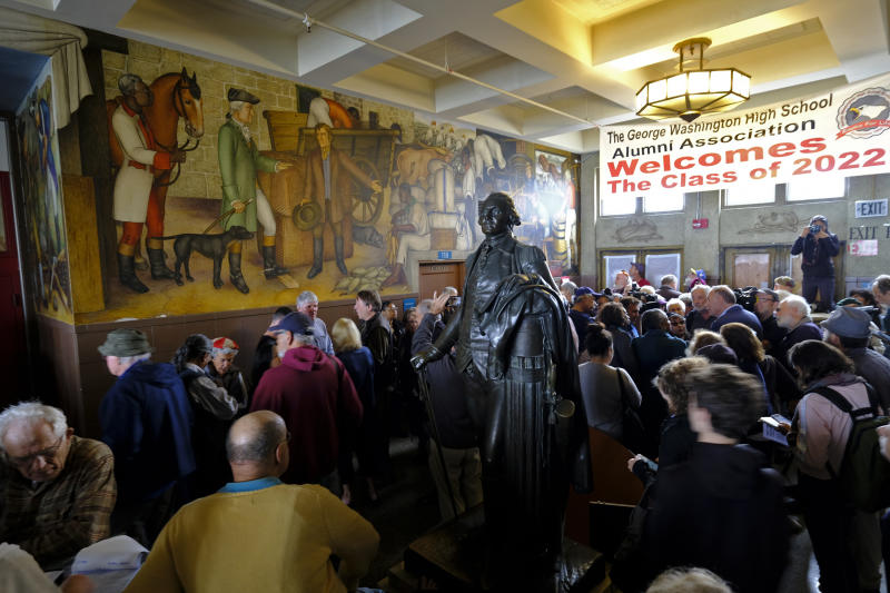 "FILE - In this Aug. 1, 2019, file photo, people fill the main entryway of George Washington High School to view the controversial 13-panel, 1,600-square foot mural, the ""Life of Washington,"" during an open house for the public in San Francisco. San Francisco Unified School District Board of Education President Stevon Cook says he plans to introduce a solution at the school board meeting Tuesday, Aug. 13, 2019, to cover the ""Life of Washington"" mural without destroying it. Cook says he will propose covering the mural with panels that contain artwork that shows ""the heroism of people of color in America, how we have fought against, and continue to battle discrimination, racism, hatred, and poverty."" (AP Photo/Eric Risberg, File)"