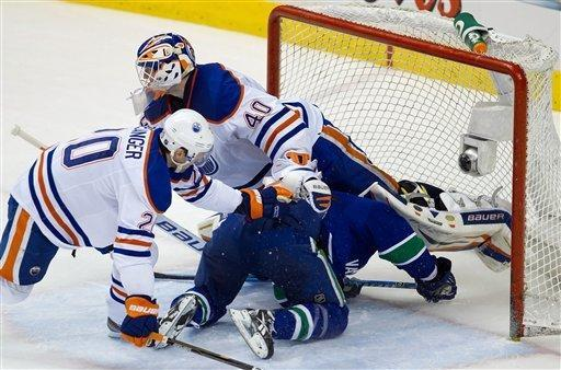 Vancouver Canucks' Alex Burrows, bottom right, crashes into Edmonton Oilers goalie Devan Dubnyk as Eric Belanger, left, trails the play during the second period of an NHL hockey game in Vancouver, British Columbia, on Tuesday, Jan. 24, 2012. (AP Photo/The Canadian Press, Darryl Dyck)