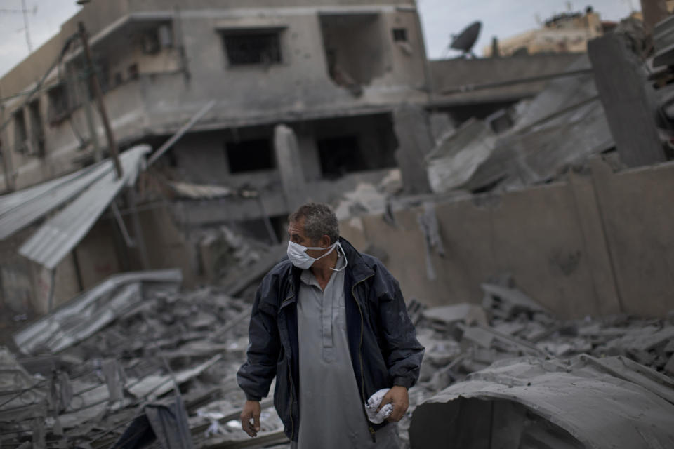 A Palestinian man walks among debris after an Israeli airstrike at Hamas Prime Minister Ismail Haniyeh's office, right, in Gaza City, Saturday, Nov. 17, 2012. Israel bombarded the Hamas-ruled Gaza Strip with more than 180 airstrikes early Saturday, widening a blistering assault on militant operations to target government and police compounds and a vast network of smuggling tunnels. (AP Photo/Bernat Armangue)