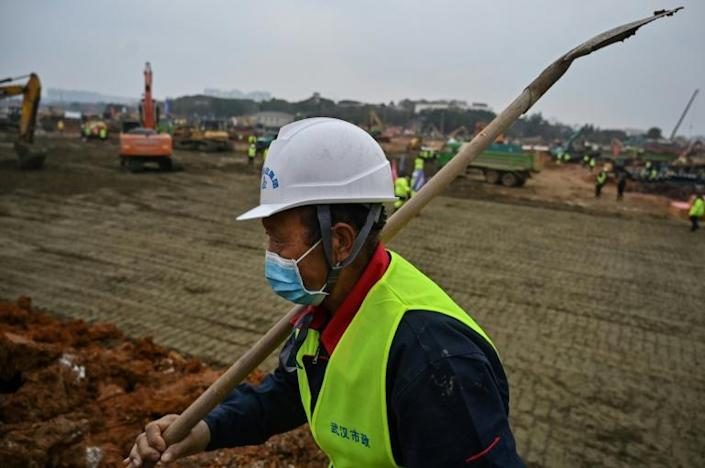 Construction workers at the sites of new hospitals in Wuhan are checked for fevers when they arrive and again during their breaks (AFP Photo/Hector RETAMAL)