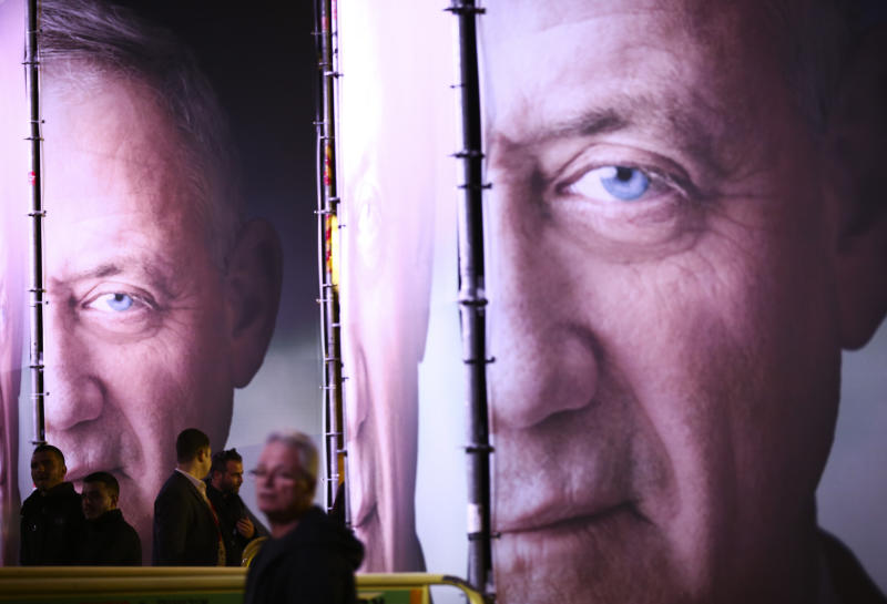 "FILE - In this Jan. 29, 2019, file photo, people walk by posters of retired Israeli military chief Benny Gantz before the official launch of his election campaign for the April 2019 elections, in Tel Aviv. Gantz has burst onto the Israeli political scene as the great hope of the country's shrinking ""peace camp"" with a message that is anything but dovish. The retired general, who hopes to topple Prime Minister Benjamin Netanyahu in April 9 elections, talks tough. In today's Israel, his ready-to-rumble rhetoric appears to be the only way to topple the long-serving Netanyahu. (AP Photo/Oded Balilty, File)"