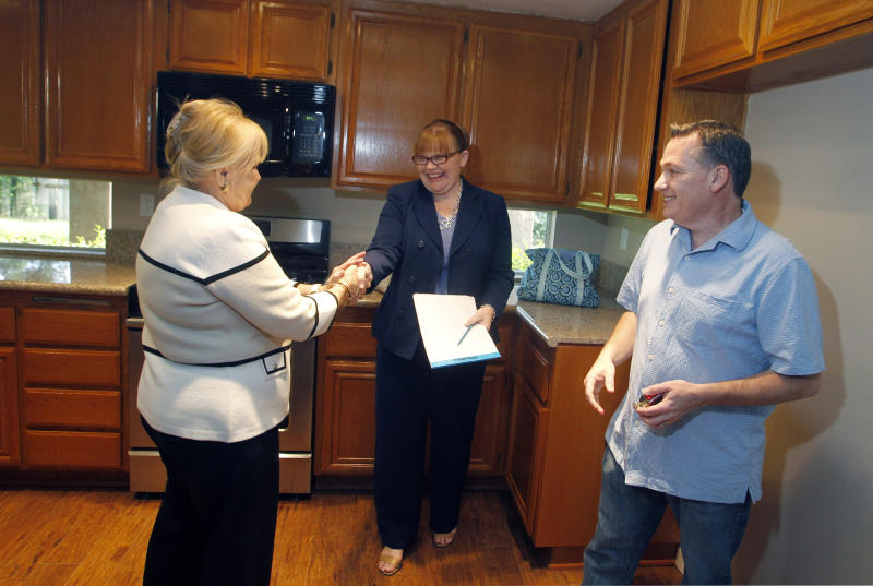 Realtor April Bolin, (L) congratulates Amy (C) and Eddie Deon after they signed papers to purchase a home in Riverside, California May 24, 2012. Six years after the housing market began its slide, dragging the U.S. economy into recession, this year's spring season - traditionally the busiest period for buying and selling houses -- is shaping up to be the strongest since the crash. Home sales rose more than 10 percent in April from a year earlier and may end the year up by as much as 13 percent, according to the National Association of Realtors. Picture taken May 24, 2012. To match Feature USA-HOUSING/RECOVERY REUTERS/Alex Gallardo (UNITED STATES - Tags: REAL ESTATE BUSINESS)