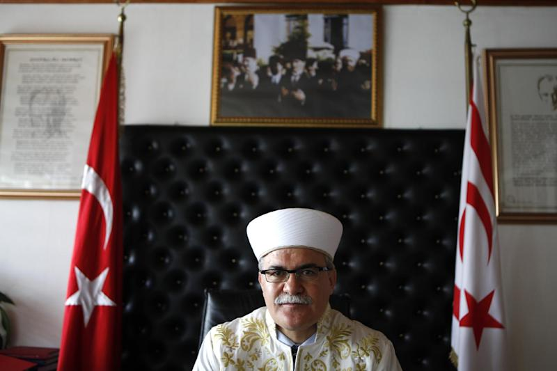 In this photo taken on Monday, April 14, 2014, Cyprus' Grand Mufti Talip Atalay, the religious affairs leader of Turkish Cypriots in the breakaway north of the ethnically split country, is seen during an interview at his office in northern part of the divided capital Nicosia. In the background are the portraits of the Turkish Cypriot leader Dervis Eroglu, left, and former Turkish Cypriot leader Rauf Denktash, centre. For the first time in nearly 60 years, a Good Friday service was held at the 14th-century church of Agios Georgios Exorinos in the medieval center of Famagusta. Cyprus was divided along ethnic lines in 1974 into a Greek Cypriot south and Turkish Cypriot north after Turkey invaded following a coup aiming to unite the island with Greece. For decades, there was no contact between the religious leaders of the Christian Greek Cypriots and Muslim Turkish Cypriots. But that changed in 2009 with a kind of faith-based diplomacy that has quietly been conducted between the leader of the island's Greek Orthodox Christian Church Archbishop Chrysostomos II and Turkish Cypriot Muslim Grand Mufti Talip Atalay. (AP Photo/Petros Kardjias)