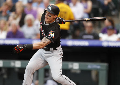 Miami Marlins' Derek Dietrich follows the flight of his solo home run off Colorado Rockies starting pitcher Jon Gray in the third inning of a baseball game Friday, June 22, 2018, in Denver. (AP Photo/David Zalubowski)