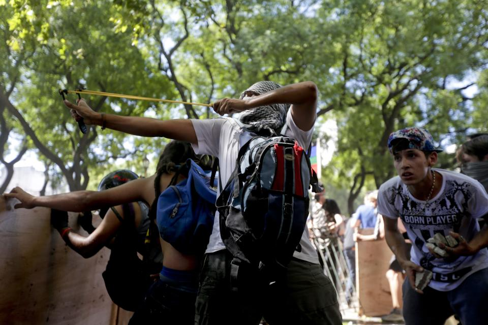 <p>A protester aims a slingshot at police during a general strike against a pension reform measure, outside Congress in Buenos Aires, Argentina, Monday, Dec. 18, 2017. Union leaders complain the legislation, which already passed in the Senate, would cut pension and retirement payments as well as aid for some of poor families. (AP Photo/Victor R. Caivano) </p>