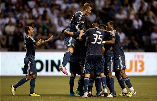 Los Angeles Galaxy's David Beckham, second left, of England, jumps into the celebration as Jose Villarreal is mobbed by his teammates after scoring the tying goal against the Vancouver Whitecaps during the second half of an MLS soccer game in Vancouver, British Columbia, on Wednesday, July 18, 2012. (AP Photo/The Canadian Press, Darryl Dyck)