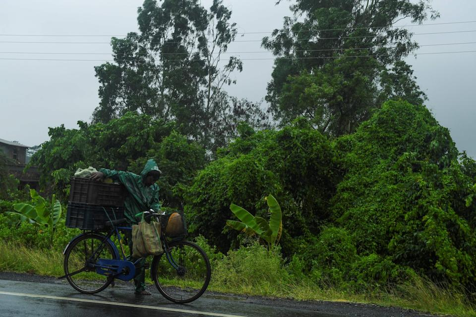 A man pushes a bicycle loaded with vegetable under the rain ahead of the expected landfall of cyclone Amphan in Midnapore, West Bengal, on May 20, 2020. (Photo by DIBYANGSHU SARKAR/AFP via Getty Images)