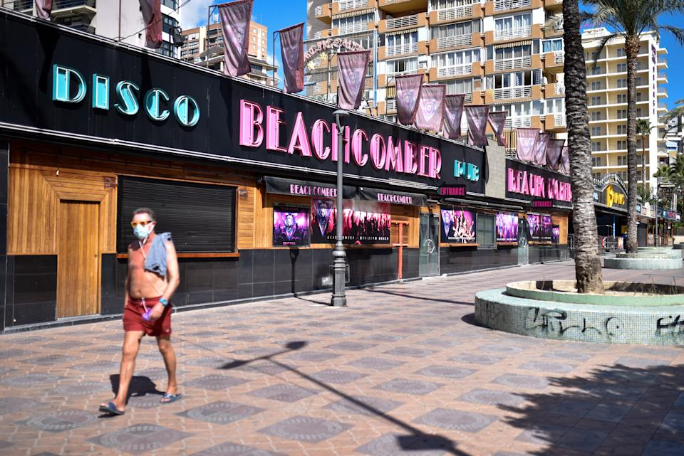 BENIDORM, SPAIN - 2020/09/09: A topless man wearing a face mask walks along Mallorca Street amid Coronavirus (COVID-19) crisis. When Spain locked down to slow the coronavirus in March, about 25,000 British tourists were enjoying the beaches and bars of the Costa Blanca resort of Benidorm. Local officials quickly ordered hotels to shut their doors, and as the visitors packed their bags and flocked to the airport, the towns tourism industryits lifebloodwent into hibernation along with the rest of the country. (Photo by Juan Zamora/SOPA Images/LightRocket via Getty Images)