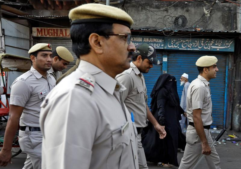 Veiled Muslim woman walk past police officers conducting a flag march in a street outside Jama Masjid, before Supreme Court's verdict on a disputed religious site claimed by both majority Hindus and Muslim in Ayodhya, in Delhi
