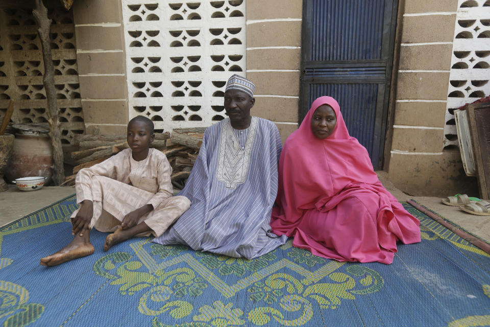 Usman Mohammad Rabiu, a 13 year old student of Government Science Secondary School Kankara, sits with his father Wada Haske and his mother Asmau Hassan at their family house in Ketare, Nigeria, and speaks to the Associated Press, Saturday Dec. 19, 2020. Nigeria's freed schoolboys have reunited with their joyful parents after being held captive for nearly a week by gunmen allied with jihadist rebels in the country's northwest. Relieved parents hugged their sons tightly on Saturday in Kankara, where more than 340 boys were abducted from the Government Science Secondary school on the night of Dec. 11. (AP Photo/Sunday Alamba)