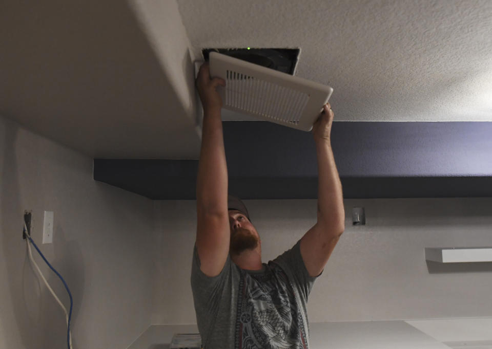 ENGLEWOOD, CO - AUGUST 30: Brandon McNitt, of McNiitt Brothers Heating, puts in a fan cover while working on a basement remodel on August 30, 2018 in Englewood, Colorado. (Photo by RJ Sangosti/The Denver Post via Getty Images)