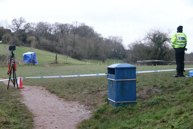 A police officer watches as a forensic tent is set up in Bugs Bottom fields in Emmer Green, Reading