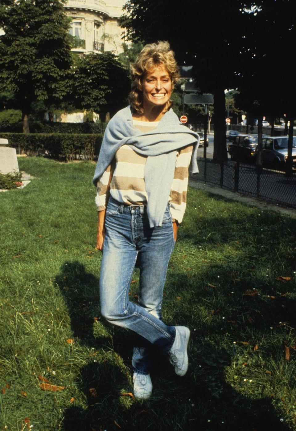 <p><em>Charlie's Angels </em>star Farrah Fawcett smiles for paparazzi in Paris. The actress, dressed comfortably in a striped sweater and jeans, was spending the day out with her then-boyfriend, French financier Arpad Busson.</p>