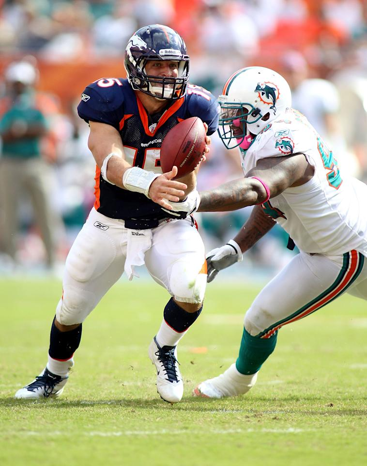 MIAMI GARDENS, FL - OCTOBER 23:  Quarterback Tim Teebow #15 of the Denver Broncos rolls out against Cameron Wake #91 of the Miami Dolphins to end the game to overtime at Sun Life Stadium on October 23, 2011 in Miami Gardens, Florida. Denver defeated Miami 18-15.  (Photo by Marc Serota/Getty Images)