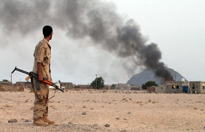 A Yemeni fighter from the Popular Resistance Committees looks towards smoke rising from a building after they reportedly attacks military vehicle belonging to Shiite Houthi rebels west of the southern embattled Yemeni city of Aden on July 12, 2015 (AFP Photo/Saleh al-Obeidi)