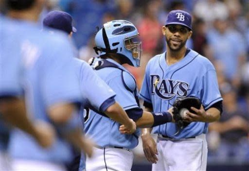 Tampa Bay Rays starting pitcher David Price, right, smiles as teammates, including catcher Jose Molina, center, come out to the mound to celebrate his complete game 3-1 win after striking out Chicago White Sox Dayan Viciedo to end a baseball game Sunday, July 7, 2013, in St. Petersburg, Fla. (AP Photo/Brian Blanco)