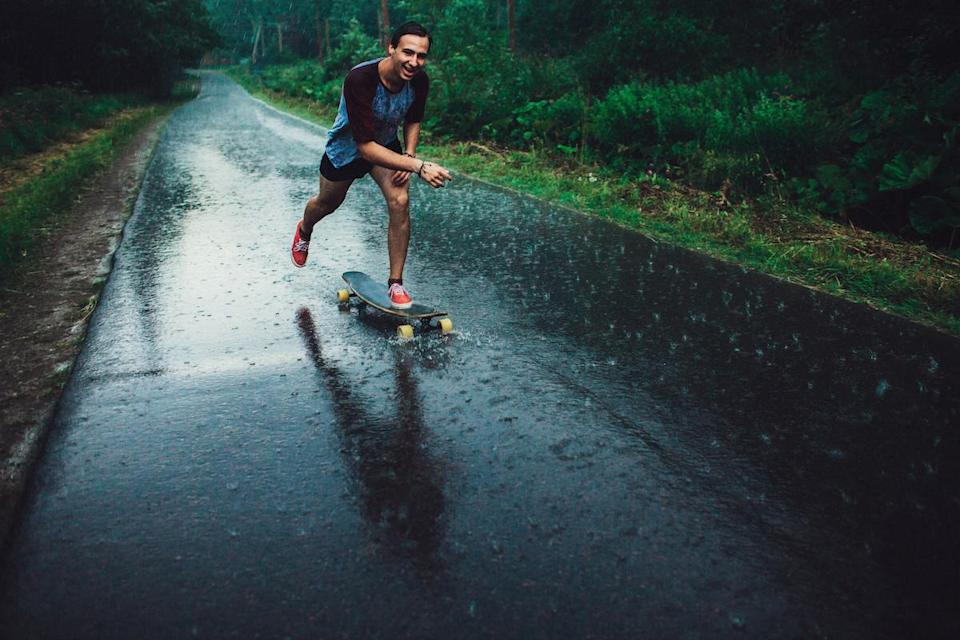 Young man longboarding in forest