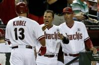 Arizona Diamondbacks' Jason Kubel (13) is congratulated by teammate Martin Prado, middle, and manager Kirk Gibson, right, after Kubel scores a run against the St. Louis Cardinals in the fourth inning during an season openingbaseball game Monday, April 1, 2013, in Phoenix. (AP Photo/Ross D. Franklin)