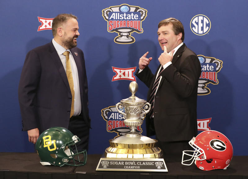 Georgia head coach Kirby Smart, right, tells Baylor head coach Matt Rhule you have to remember to smile during their photo opportunity with the Sugar Bowl trophy during an during an NCAA college football press conference, Tuesday, Dec. 31, 2019, in New Orleans. (Curtis Compton/Atlanta Journal-Constitution via AP)