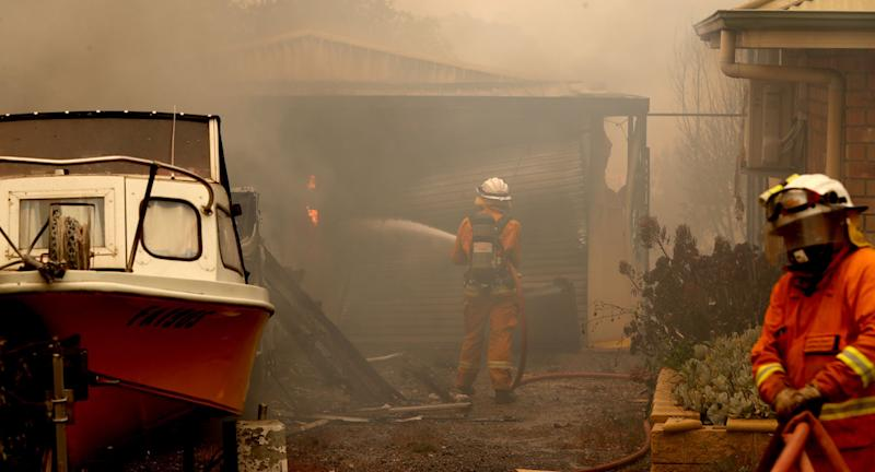 CFS firefighters put out fires on Jacaranda Drive at Woodside in the Adelaide Hills in Adelaide.