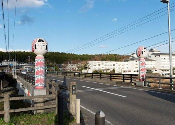 ▲ Large kokeshi dolls stand at each end of the bridge. See if you can also spot the small kokeshi dolls on the bridge.