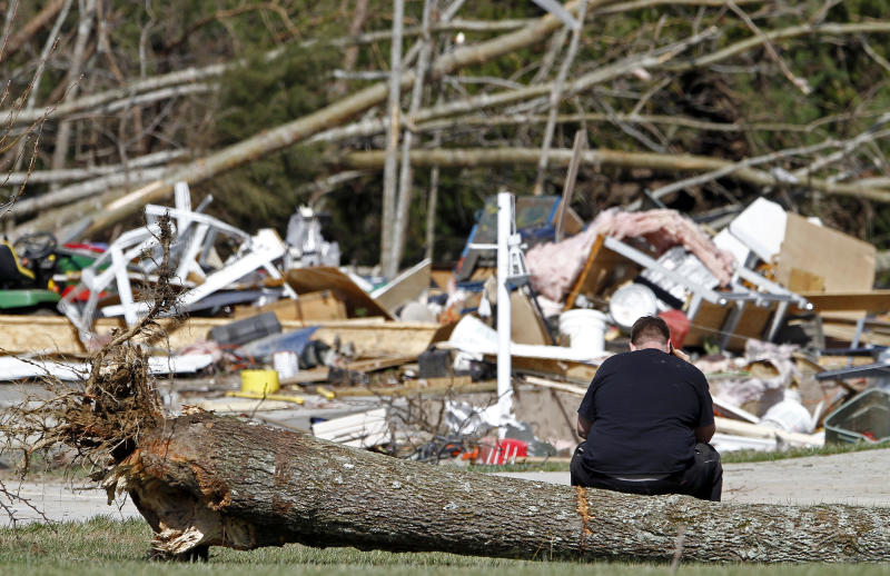 Mike Hatheway sits on a tree uprooted by a deadly tornado as he talks on the phone at the remains of his grandparents home in the Rinnie Community near Crossville, Tenn. Thursday, March 1, 2012. His grandmother Carolyn Jones was killed and his grandfather Harold Jones was taken to the hospital. A pre-dawn twister flattened entire blocks of homes Wednesday as violent storms ravaged the Midwest and South. (AP Photo/Wade Payne)