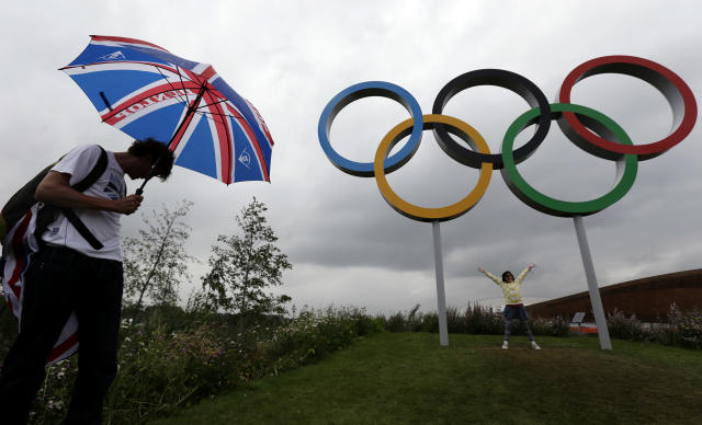 A fan shields himself from the rain with an umbrella as he wait to pose with the Olympic rings near the basketball arena at the 2012 Summer Olympics, Tuesday, July 31, 2012, in London. (AP Photo/Eric Gay)