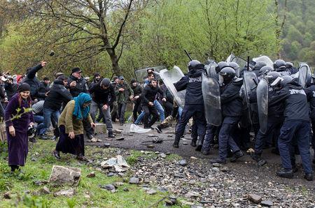 Participants attack police officers during a rally held by residents of the Pankisi gorge, who protest against the planned construction of a hydropower plant, near the village of Birkiani, Georgia April 21, 2019. REUTERS/Ekaterina Anchevskaya