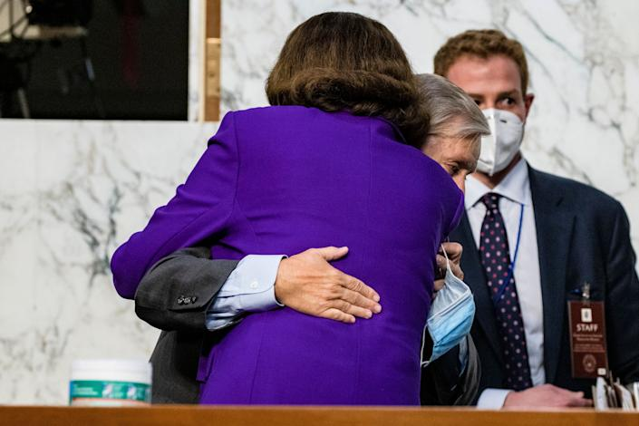 Sen. Dianne Feinstein (D-Calif.) hugs Sen. Lindsey Graham (R-S.C.) as the confirmation hearings for Supreme Court nominee Judge Amy Coney Barrett come to a close on Thursday. Neither senator wore a mask. (Photo: Samuel Corum via Getty Images)