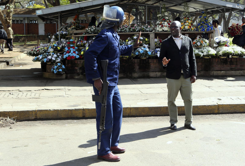 An armed riot policeman gestures to a pedestrian in Harare, Friday, Aug, 16, 2019. Zimbabwe's police patrolled the streets of Harare Friday morning while many residents stayed home and shops were shut fearing violence from an anti-government demonstration. Zimbabwe's High Court has upheld the police ban on the opposition protest.(AP Photo/Tsvangirayi Mukwazhi)