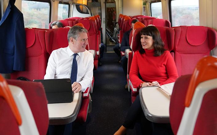 Labour leader Sir Keir Starmer speaking to shadow chancellor Rachel Reeves as they travel by train to Sheffield - PA
