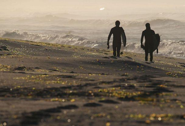 PHOTO: Surfers head to the beach in the early morning hours on April 25, 2020 in Long Beach, N.Y. (Bruce Bennett/Getty Images)