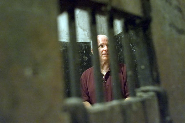 """<p>John McCain walks inside the Hoa Lo prison, nicknamed """"The Hanoi Hilton"""" in Hanoi, Vietman, on April 27, 2000, where McCain was kept as a prisoner of war from October 1967 until March 1973. McCain was visiting as Vietnam marked the 25th anniversary of the end of the war. (Photo: David Guttenfelder/AP) </p>"""