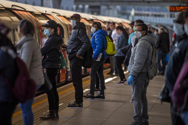 Passengers wearing face masks on a platform at Canning Town underground station in London. (PA)