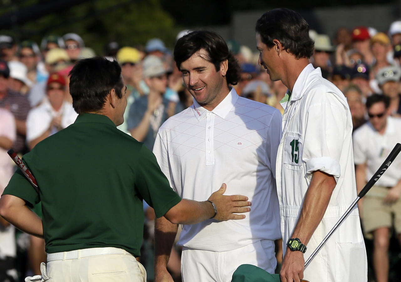 Louis Oosthuizen, left, of South Africa, congratulates Bubba Watson on the 18th green following their fourth round of the Masters golf tournament Sunday, April 8, 2012, in Augusta, Ga. At right is Watson's caddie Chad Reynolds. (AP Photo/David J. Phillip)