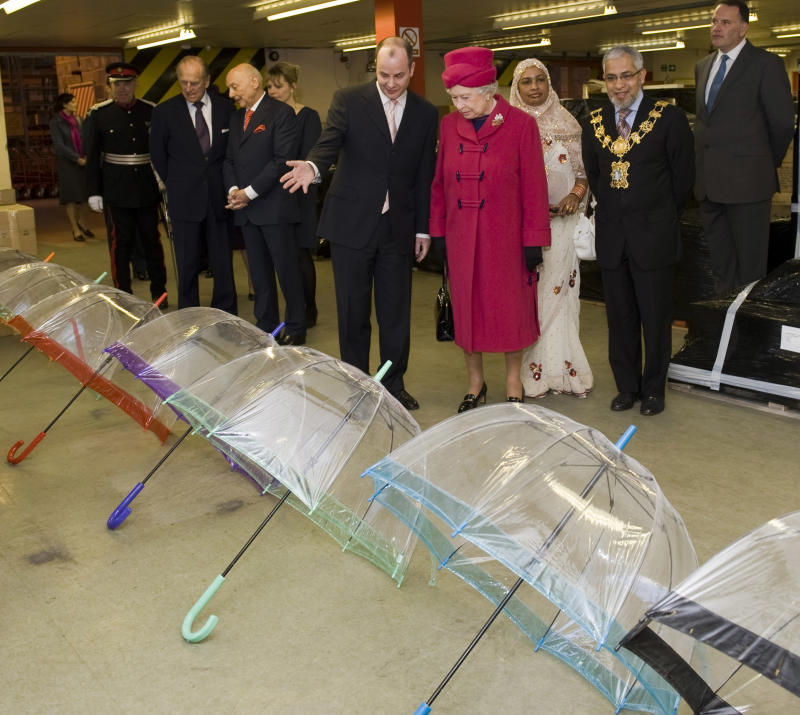 LONDON - MARCH 25: Prince Philip, Duke of Edinburgh (2L) and Queen Elizabeth II (4R) visit Fulton Umbrellas factory on the Isle of Dogs on March 25, 2009 in London, England. During the visit the Queen Duke of Edinburgh were shown various stages in the production and assembly of the umberellas. (Photo by Arthur Edwards-Pool/Getty Images)