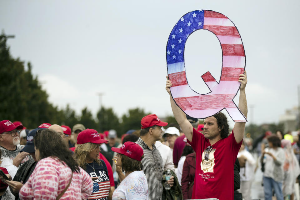 """FILE - In this Aug. 2, 2018, file photo, David Reinert holding a Q sign waits in line with others to enter a campaign rally with President Donald Trump in Wilkes-Barre, Pa. A far-right conspiracy theory forged in a dark corner of the internet is creeping into the mainstream political arena. It's called QAnon, and it centers on the baseless belief that President Donald Trump is waging a secret campaign against enemies in the """"deep state.""""  (AP Photo/Matt Rourke, File)"""