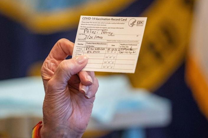 Speaker of the House Nancy Pelosi holds up a Vaccination Record Card after receiving a Covid-19 vaccine shot  (POOL/AFP via Getty Images)
