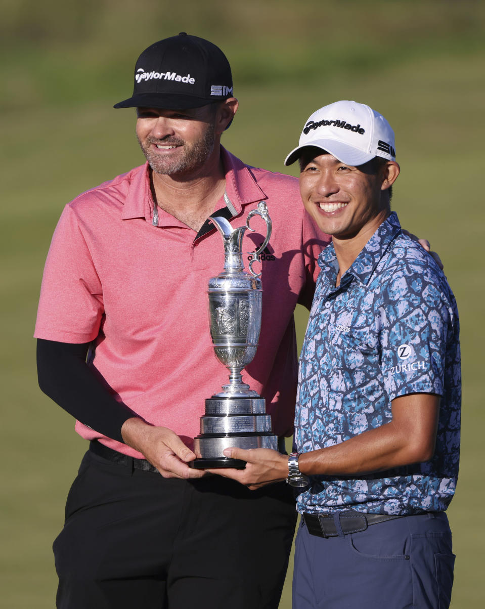United States' Collin Morikawa, right with his caddie Jonathan Jakovac as he holds up the claret jug trophy as they pose for photographers on the 18th green after winning the British Open Golf Championship at Royal St George's golf course Sandwich, England, Sunday, July 18, 2021. (AP Photo/Ian Walton)