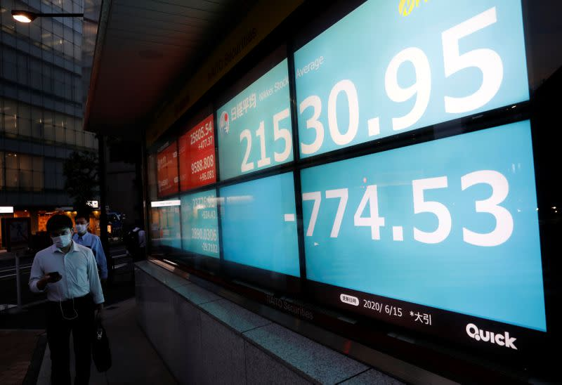 FILE PHOTO: Men wearing protective face masks, following the coronavirus disease (COVID-19) outbreak, walk past a stock quotation board outside a brokerage in Tokyo