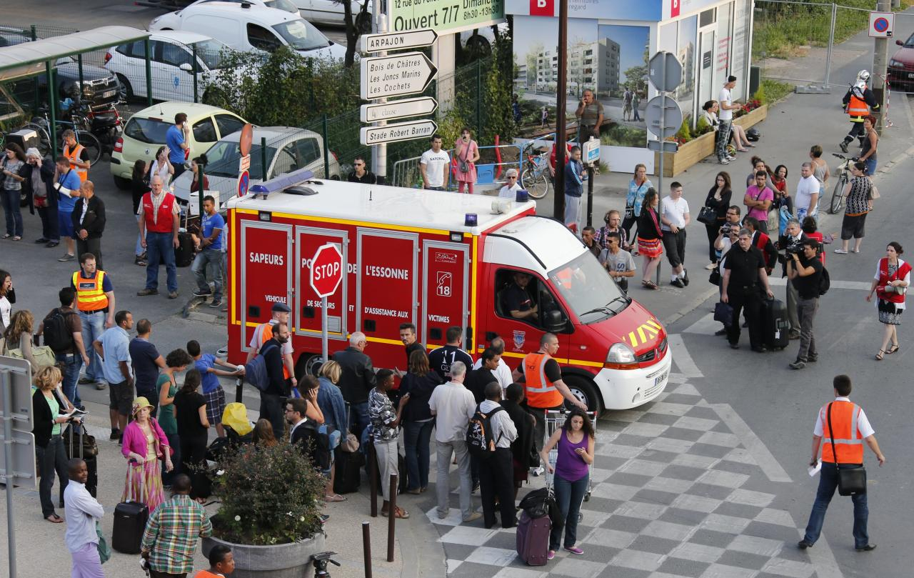 An ambulance leaves the site of an intercity train accident at the Bretigny-sur-Orge station near Paris July 12, 2013. An intercity train headed for the central French city of Limoges derailed south of Paris on Friday, the national rail company SNCF said. At least six people died and several dozen were injured, twenty-two of them seriously, when a regional train derailed en route from Paris to the central city of Limoges, French President announced during a visit on site. REUTERS/Benoit Tessier (FRANCE - Tags: TRANSPORT DISASTER)