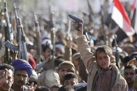 A boy shouts slogans as he raises a gun during a rally against U.S. support to Saudi-led air strikes, in Yemen's capital Sanaa