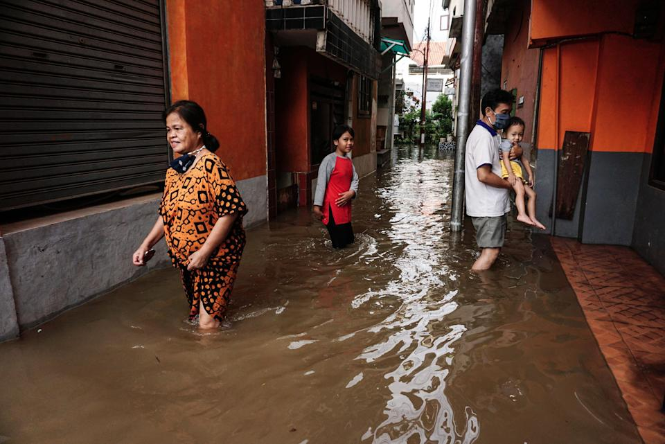 People walk through floodwater after heavy rain at a residential area in Jakarta, Indonesia (Picture: Getty)