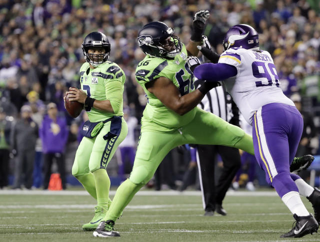 Seattle Seahawks quarterback Russell Wilson, left, looks for room to pass as Jordan Simmons (66) tries to hold back Minnesota Vikings' Linval Joseph Minnesota Vikings in the first half of an NFL football game, Monday, Dec. 10, 2018, in Seattle. (AP Photo/Ted S. Warren)