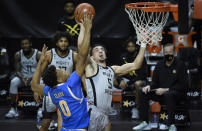 Oregon guard Chris Duarte (5) is fouled by UCLA guard Jaylen Clark (0) as he drives to the basket during the second half of an NCAA college basketball game Wednesday, March 3, 2021, in Eugene, Ore. (AP Photo/Andy Nelson)