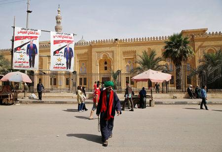 People walk in front of posters of Egypt's President Abdel Fattah al-Sisi in front of an old mosque during the preparations for tomorrow's presidential election in Cairo, Egypt March 25, 2018. REUTERS/Ammar Awad