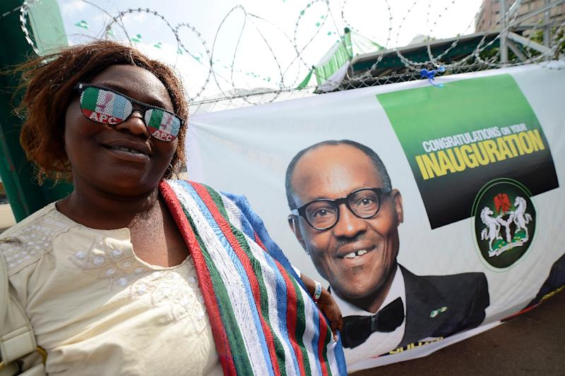 A party supporter wearing All Progressives Congress Party glasses poses with a banner for president-elect Muhammadu Buhari ahead of Friday's handover ceremony in Abuja on May 28, 2015 (AFP Photo/Pius Utomi Ekpei)