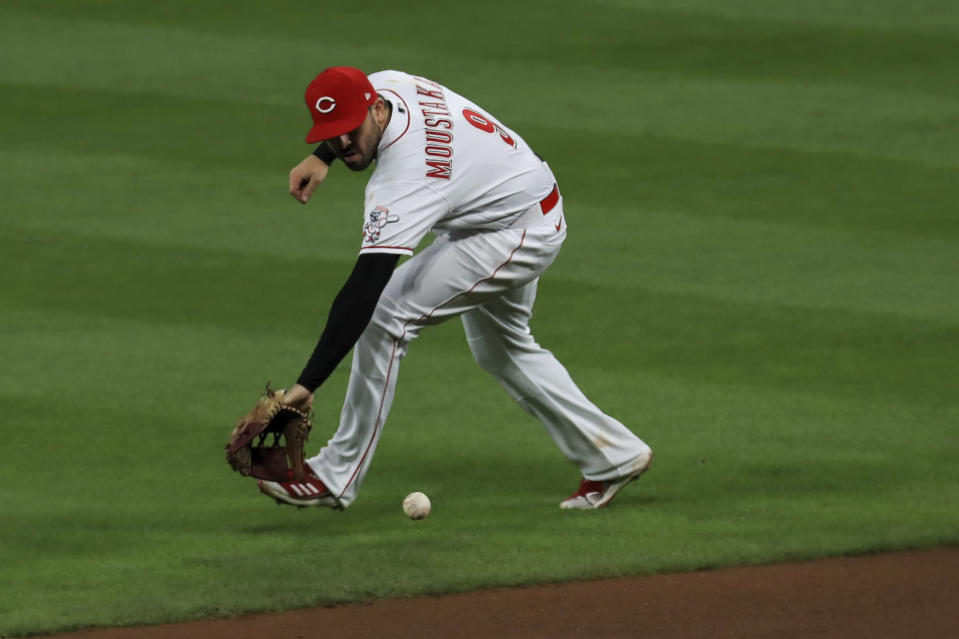 Cincinnati Reds' Mike Moustakas fields the ball after Chicago White Sox's Jose Abreu hit for a single in the fourth inning during a baseball game in Cincinnati, Saturday, Sept. 19, 2020. (AP Photo/Aaron Doster)