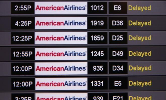 A board shows delayed American Airlines flights at Miami International Airport on April 16.