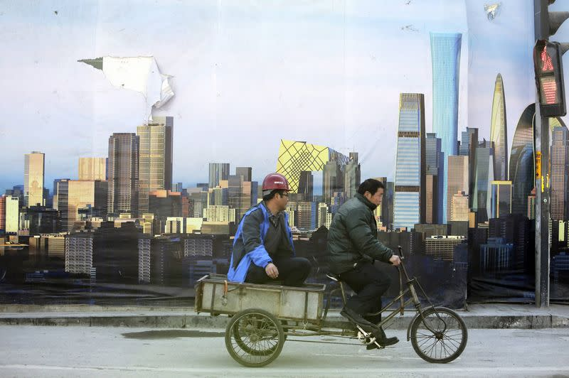 A worker rides past a poster showing Beijing's central business district outside a construction site in Beijing